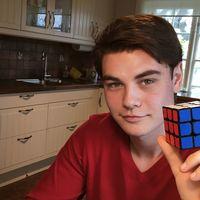 Mattias Uvesten håller upp en Rubiks kub med den blå sidan mot kameran