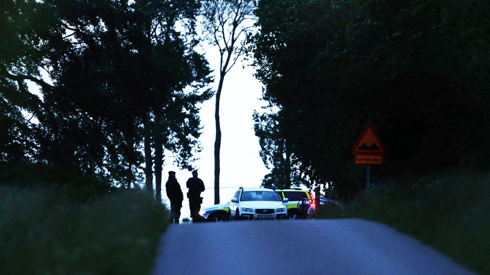 Poliser utanför den gård där två personer hittades döda måndagen den 12 juni.