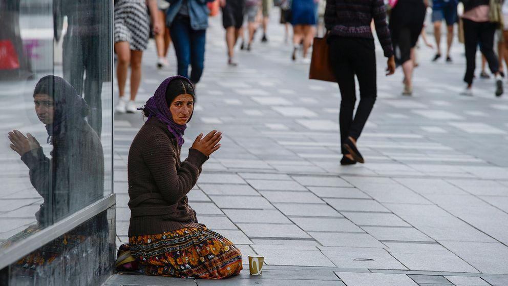 En kvinna tigger vid Sergels torg i Stockholm.