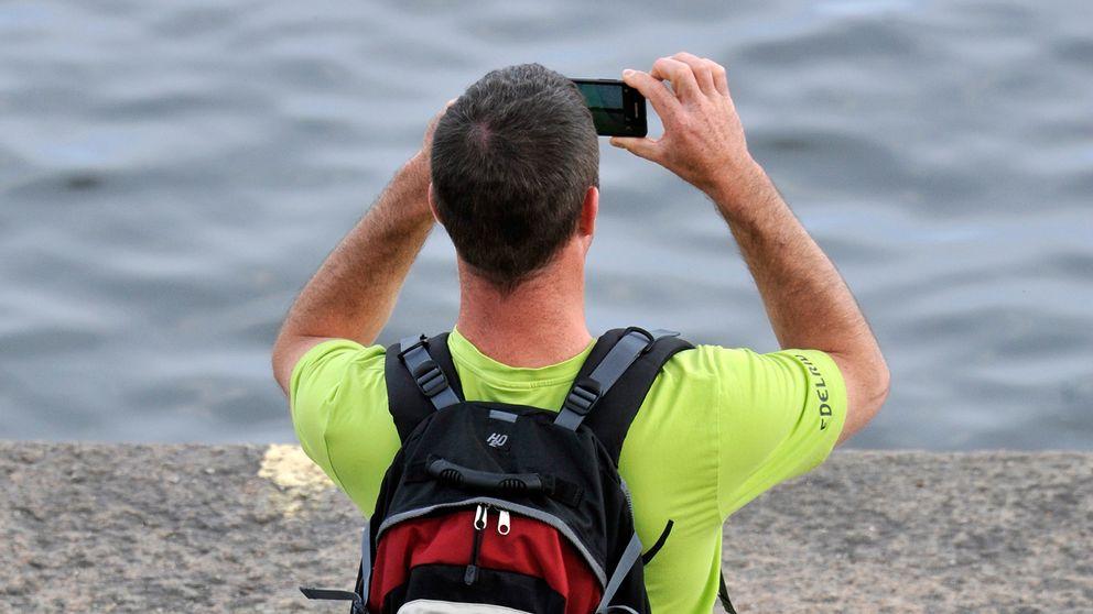 man sedd bakifrån, fotar ut över vatten med mobilen