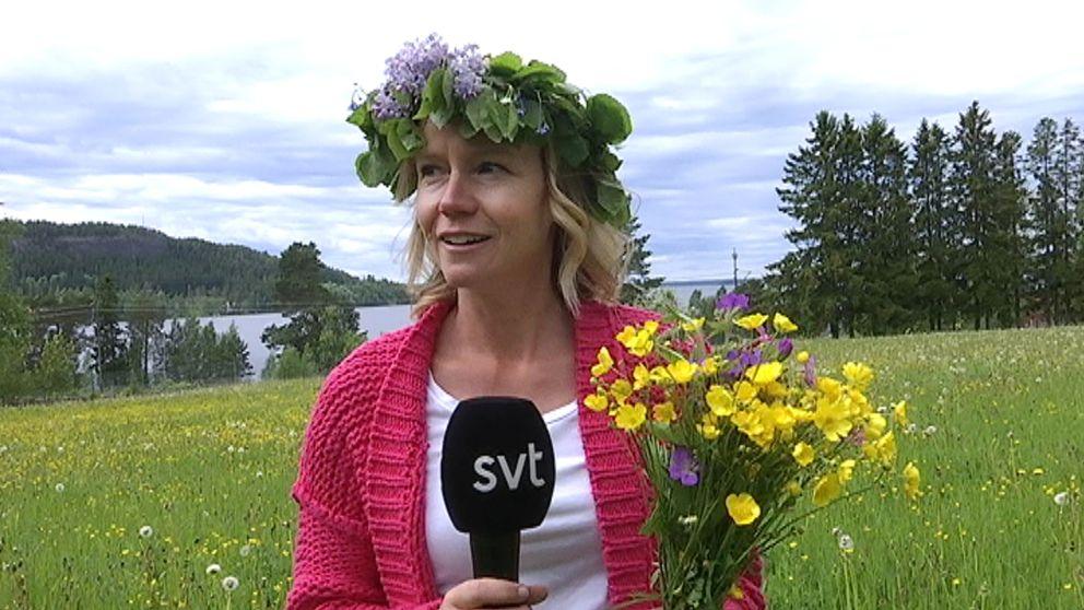 kvinna på äng med blomsterkrans och bukett