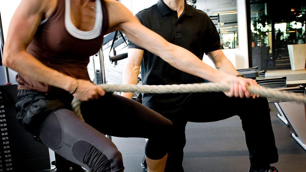 Träning med PT på gym. Arkivbild.