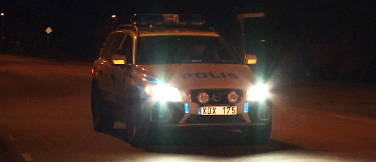 En polisbil i mörkret.