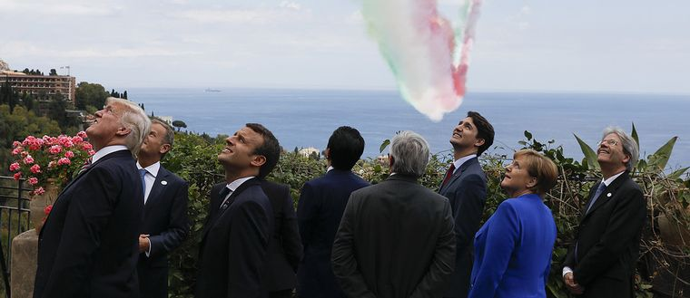 From left, President Donald Trump, European Council President Donald Tusk, Britain's Prime Minister Theresa May, French President Emmanuel Macron, Japanese Prime Minister Shinzo Abe, European Commission President Jean-Claude Juncker, Canadian Prime Minister Justin Trudeau, German Chancellor Angela Merkel and Italian Prime Minister Paolo Gentiloni watch an Italian flying squadron as part of activities at the G7 Summit in Taormina, Sicily, Italy, Friday, May 26, 2017. (Jonathan Ernst/Pool Photo via AP)