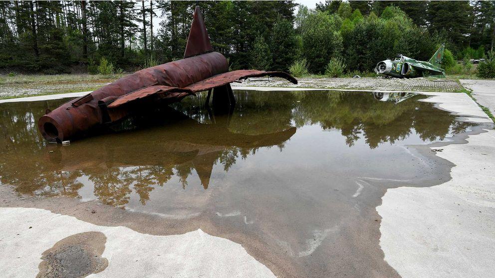 Ett rostigt flygplan ligger i en vattenpöl.