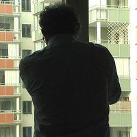 Anonym man står och tittar ut genom ett fönster i ett bostadsområde.