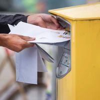 Brev som läggs i en av Postnords gula postlådor.