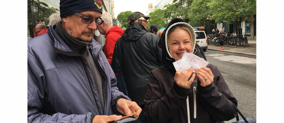 medelålders man och ung kvinna med biljetter, ute på på gatan
