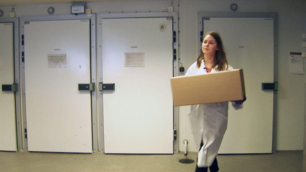 Kvinna med vit rock bär ett paket.