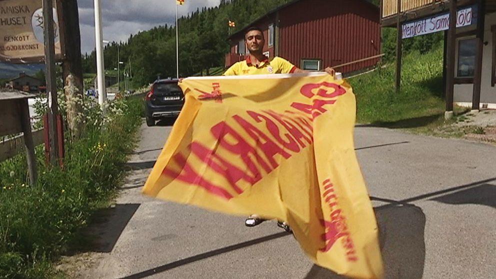 man viftar med lagets flagga