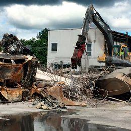 Bilar som förstörts i en brand vi bilföretaget Rejmes, samt en grävskopa som utför rivningsarbete.