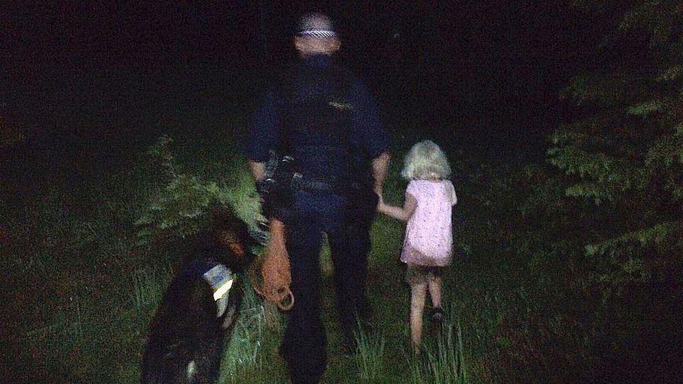 Hundföraren, polishunden Attack samt flickan sedd bakifrån när de går genom skogen.