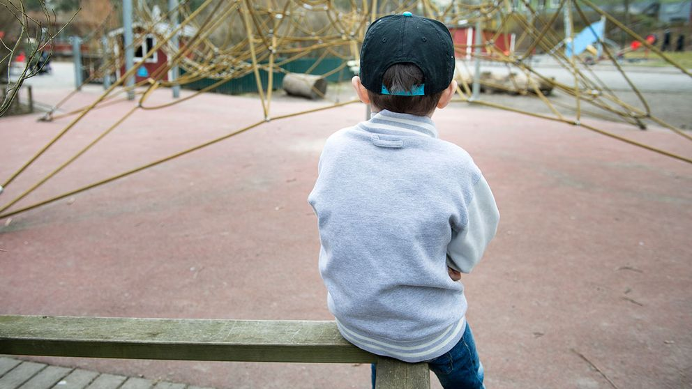 Ledset barn framför klätterställning