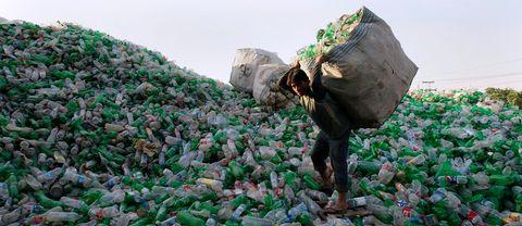 Arbetare bär plastflaskor på ett berg av flaskor vid en återvinningscentral i Lahore, Pakistan.