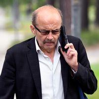 Kammaråklagaren med en telefonlur vid örat ute i friska luften.