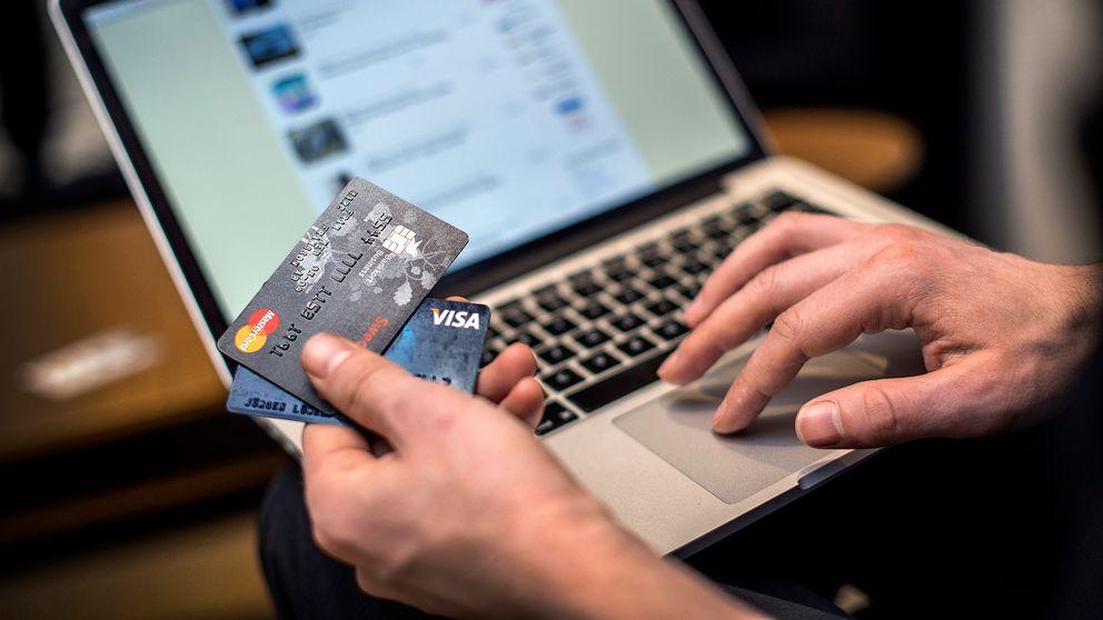 En person sitter vid datorn med kreditkort.