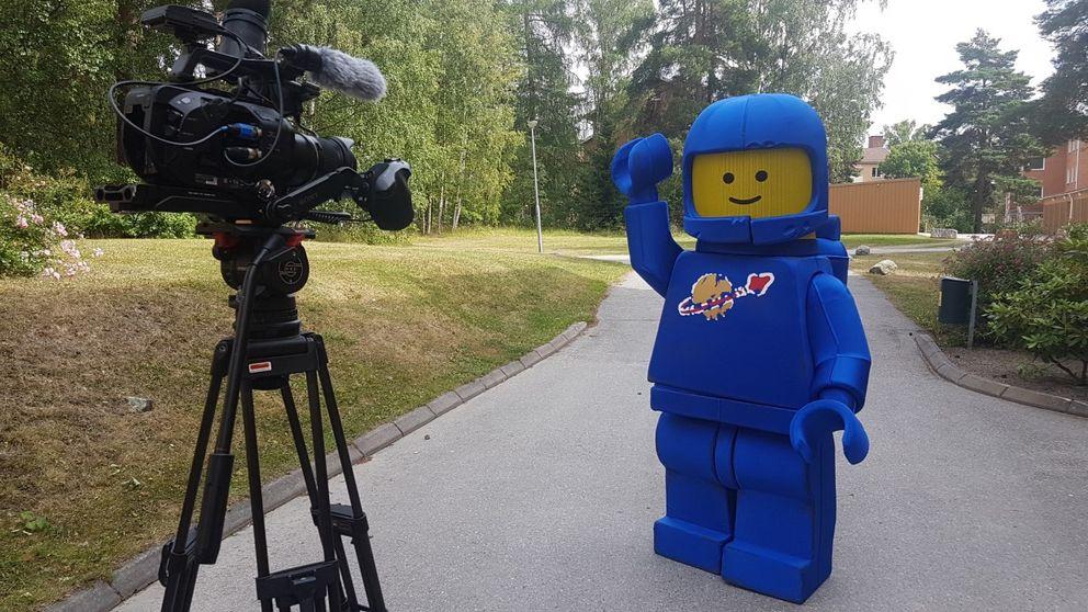 Filmkamera vänd mot en dräkt utformad som en legogubbe i förstorad storlek.
