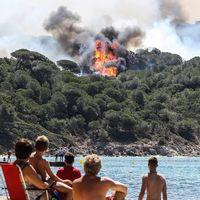 Till vänster: Strandbesökare i La Croix-Valmer, nära Saint-Tropez, ser på en skogsbrand på avstånd. Till höger: En kvinna kramar om en brandman på en eldhärjad parkering för husbilar i Bormes-les-Mimosas.