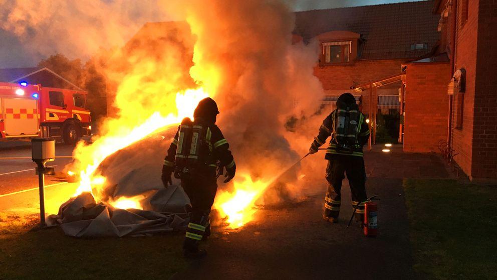 Två brandmän släcker en stor eld.
