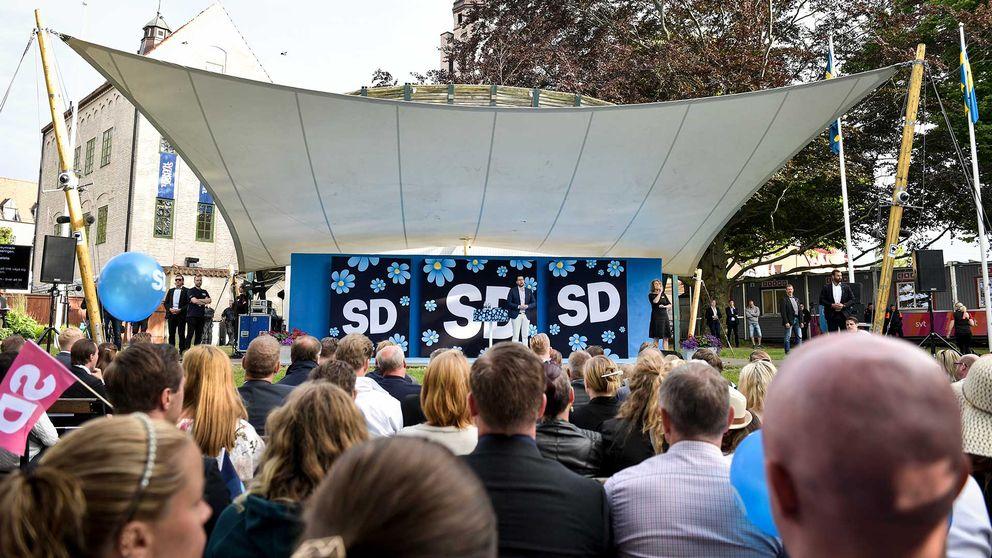 Sverigedemokraternas partiledare Jimmie Åkesson på scenen i Almedalen i Visby. Man ser personer bakifrån som tittar på när han talar.