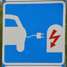 Skylt för laddning av elbil med grön suddig bakgrund.