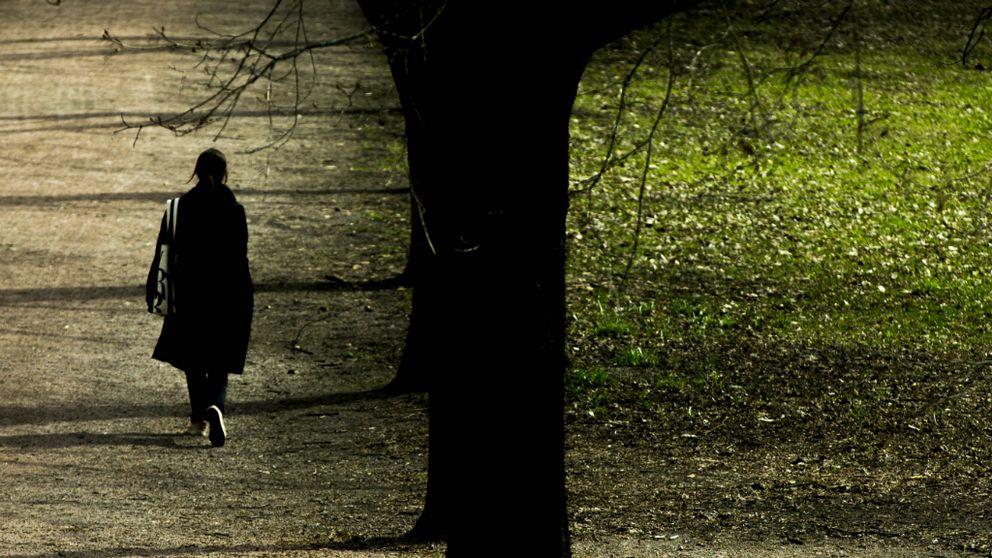 Kvinna promenerar i en park