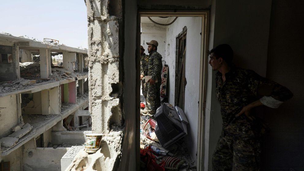 Stridande medlemmar av YPG och SDF genomsöker förstörda byggnader i Raqqa, Syrien.