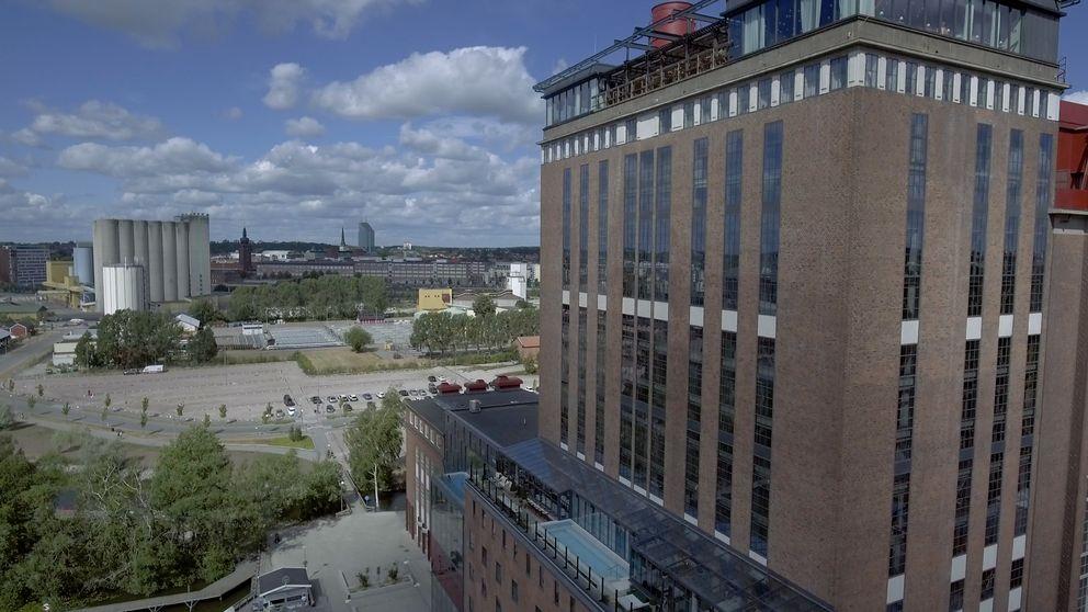 Gammal fabriksbyggnad, ett ångkraftverk i Västerås och Västerås i bakgrunden.