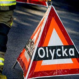 En person från räddningstjänsten står bredvid en olyckstriangel.