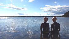 Två personer som sysslar med swimrun står i vattnet och tittar på varandra.
