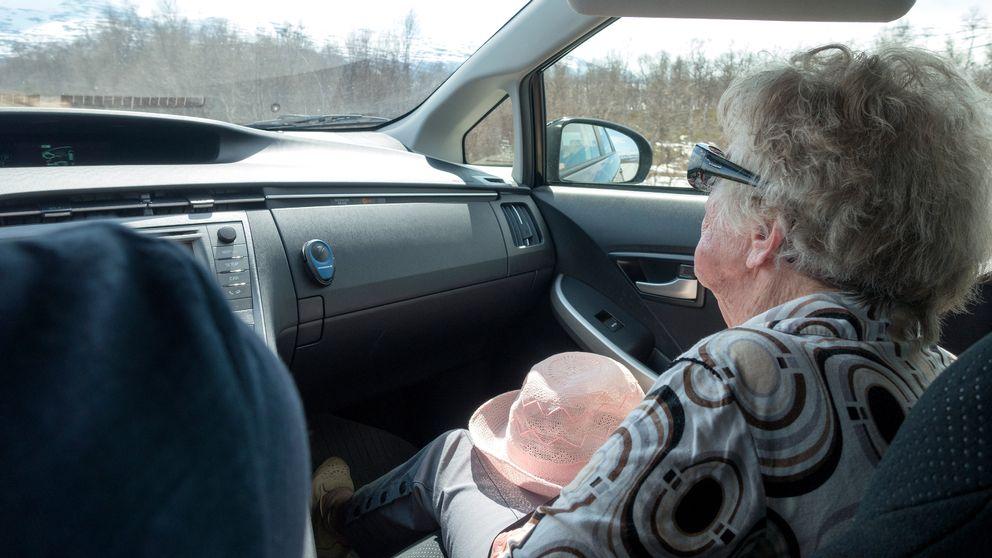 Äldre kvinna sitter i passagerarsätet i en bil.