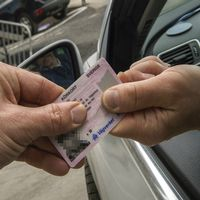 Två händer håller ett körkort.