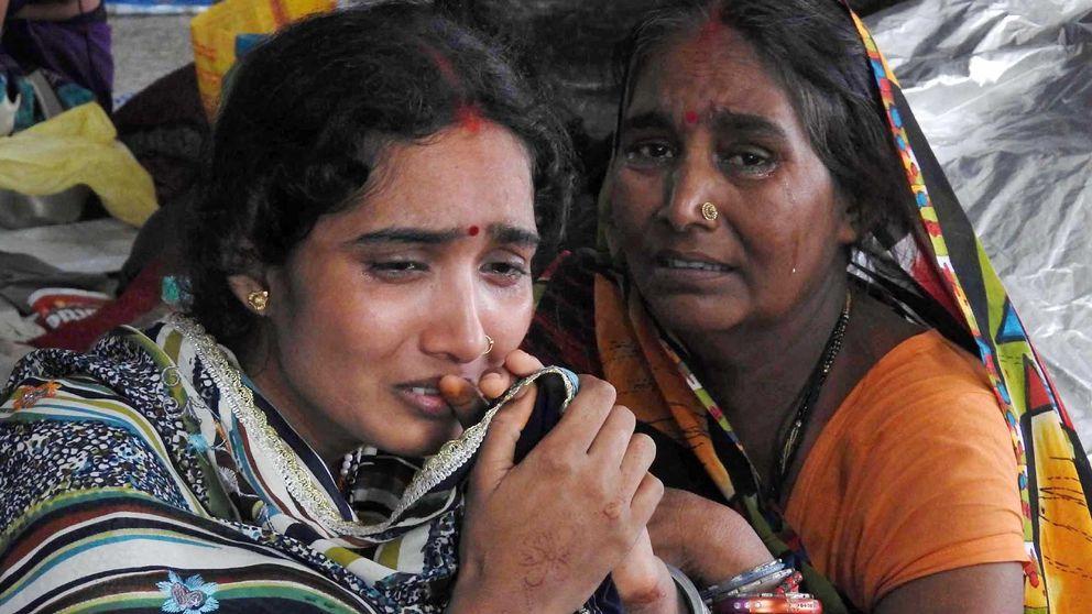 Två indiska kvinnor som gråter tröstar varandra.