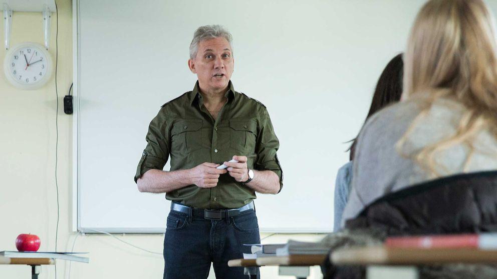 Man står och pratar i ett klassrum inför elever. En klocka syns i bakgrunden på väggen och på bänken framför honom ligger ett rött äpple.