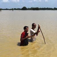 Två män korsar floden i byn Tilathi i Saptari-distriktet, 450 km sydost Kathmandu, Nepal