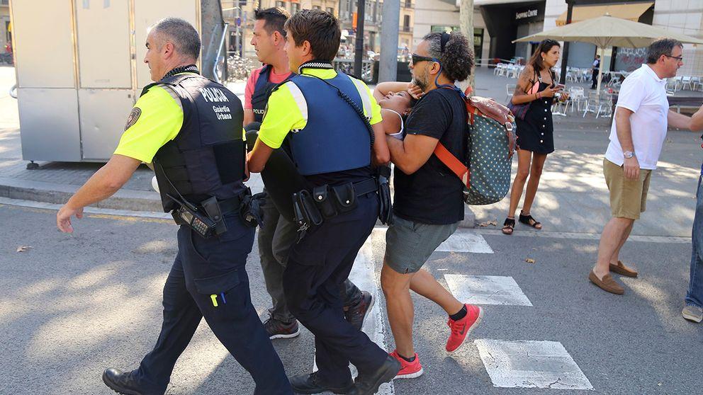 En skadad kvinna bärs i väg av polis och civila.