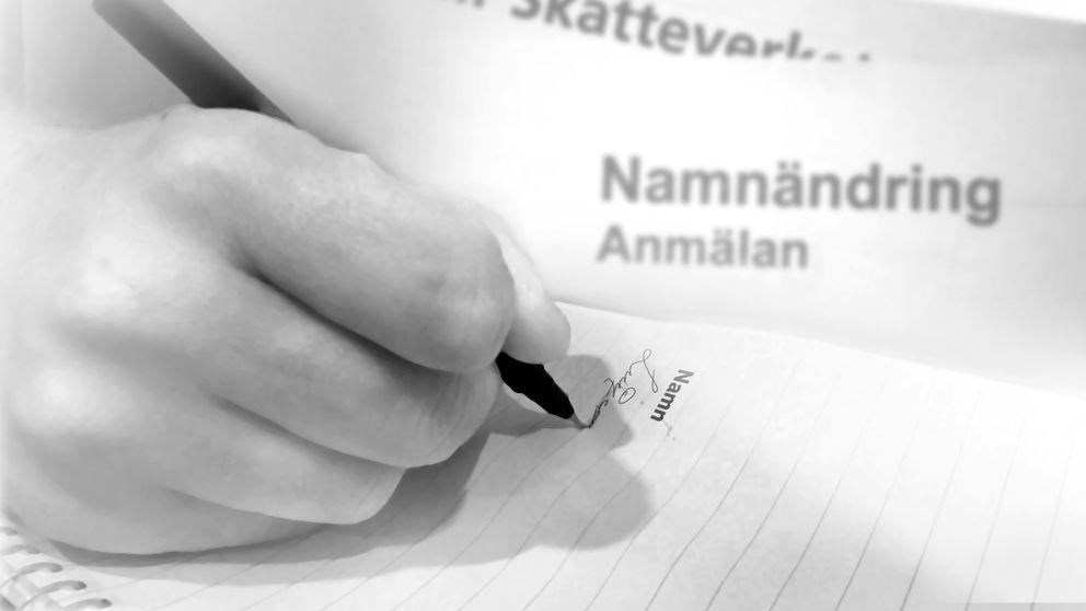 En hand som håller i en penna och som skriver Lucifer på ett papper.