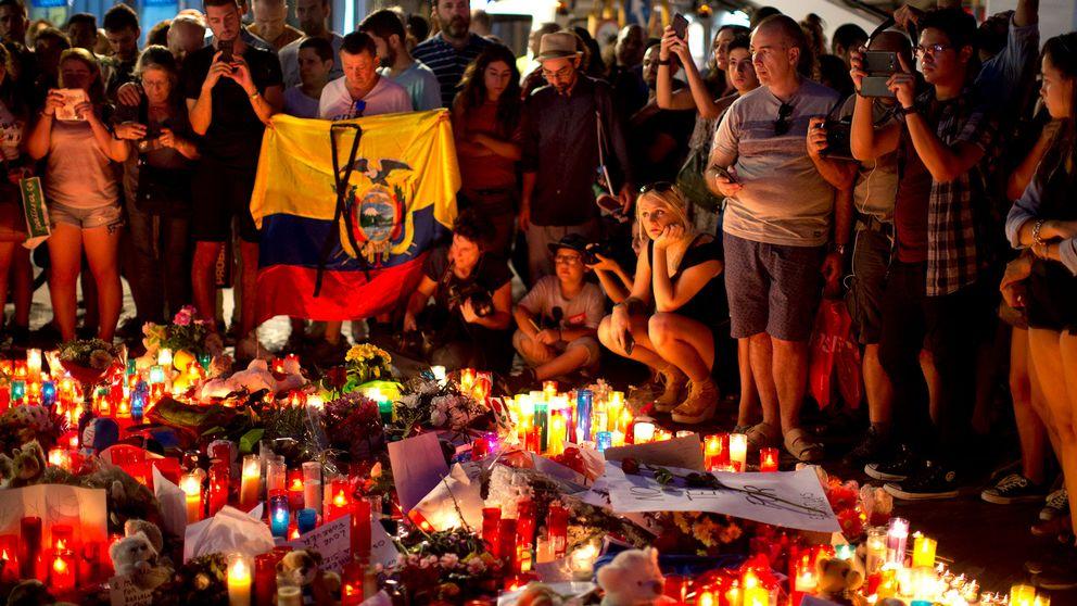 Människor samlas kring en minnesplats fylld av ljus och blommor i Barcelona