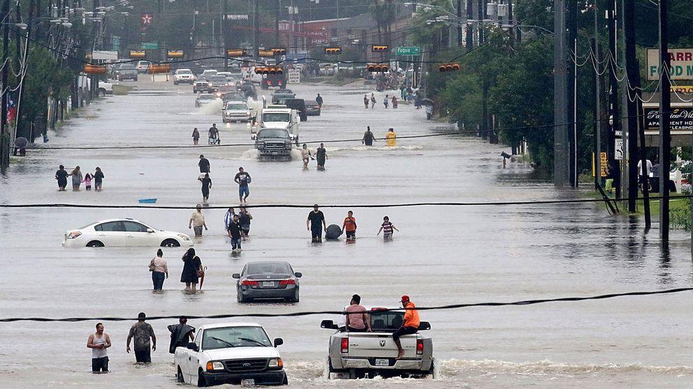 Människor vadar fram på Telephone road i södra Houston. Staden, som är USA:s fjärde folkrikaste, har drabbats av massiva översvämningar de senaste dygnen.