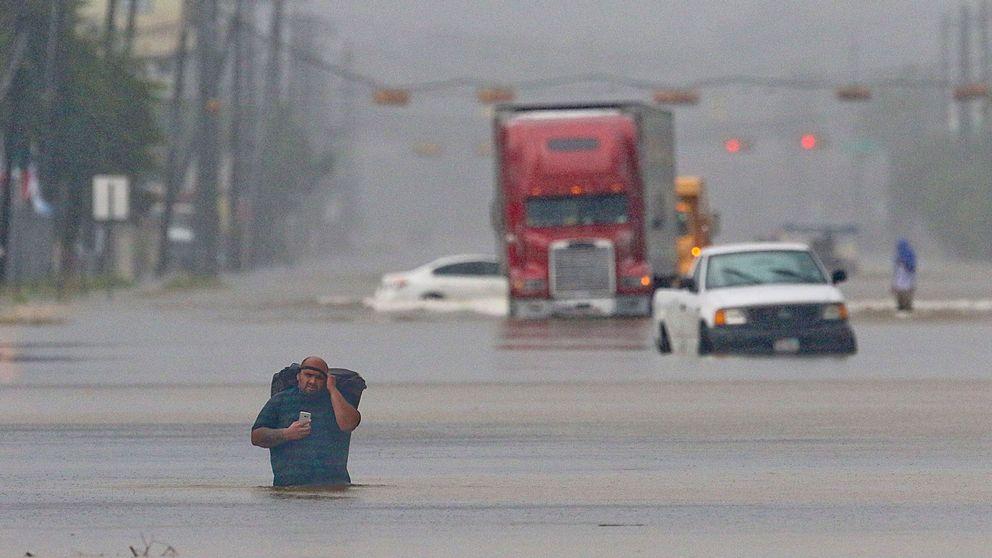 En man bär med sig sina tillhörigheter medan han tar sig fram på en översvämmad gata i Houston, Texas den 27 augusti.