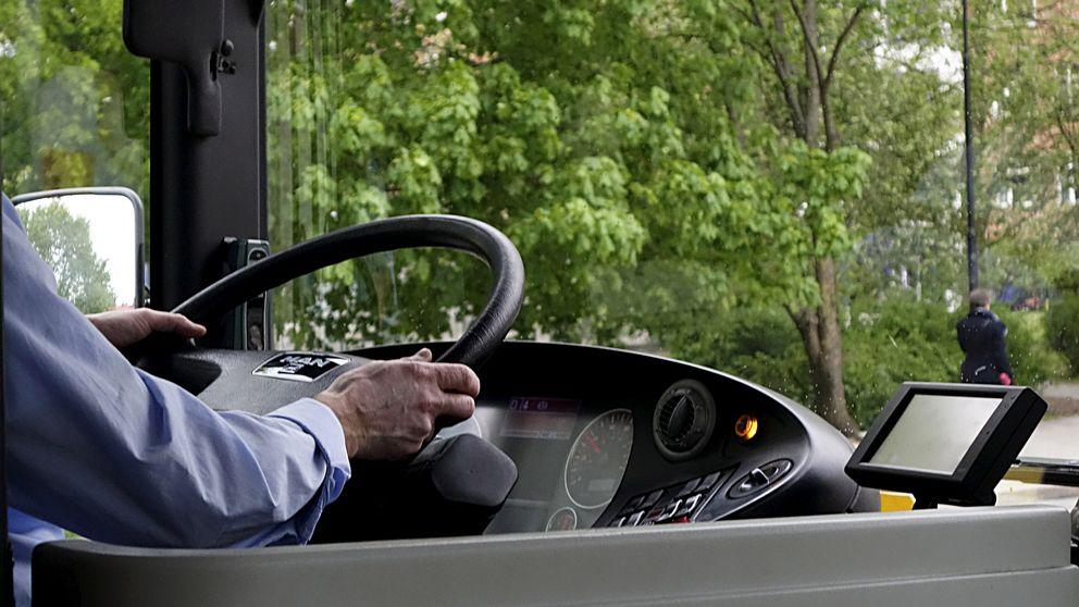 Armarna på en busschaufför som håller i ratten.