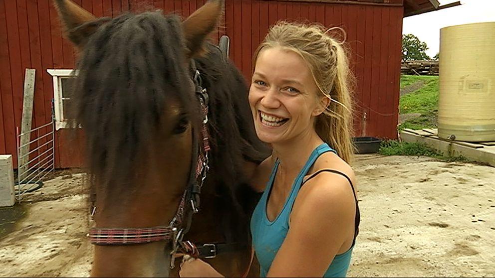 tjej med blont hår och hästsvans bredvid häst utanför ladugård