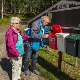 ett äldre par tittar i brevlådan längs en grusväg