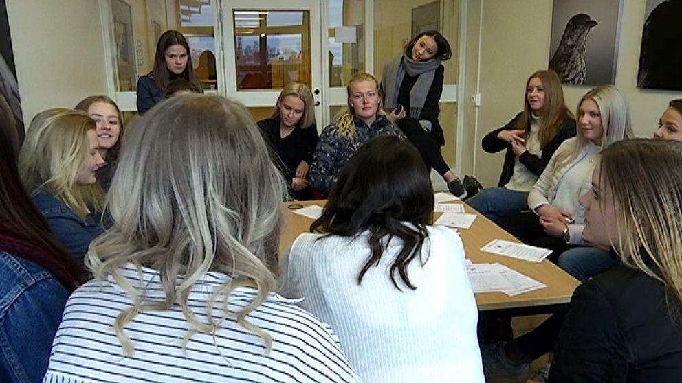 Gymnasieelever, alla tjejer, sitter runt ett bord och pratar med varandra.
