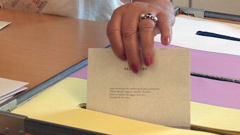 En hand som lägger en valsedel i en röstlåda, kyrkovalet