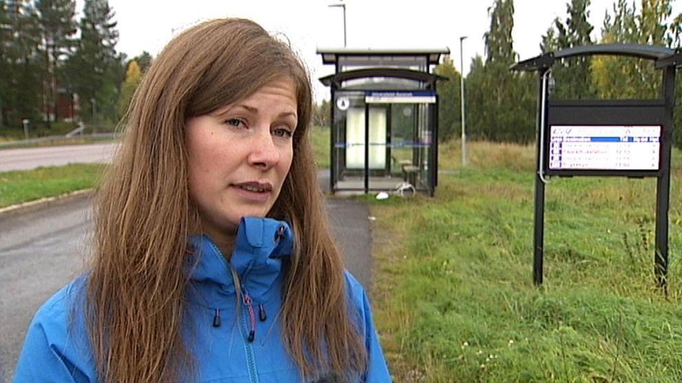 Kvinna intervjuas vid busshållplats.