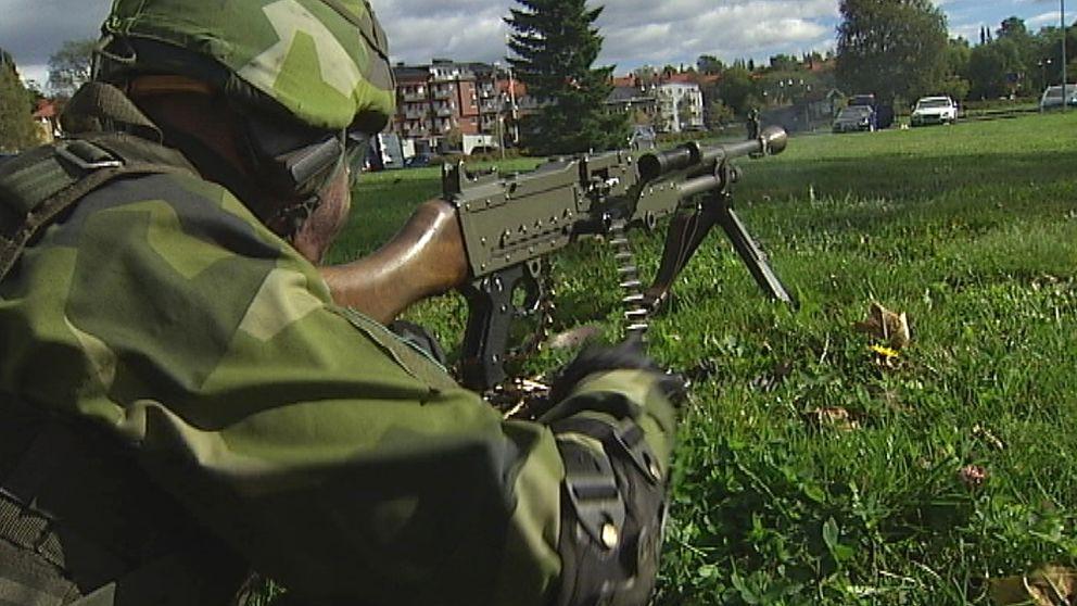 Soldat med vapen i stadsmiljö