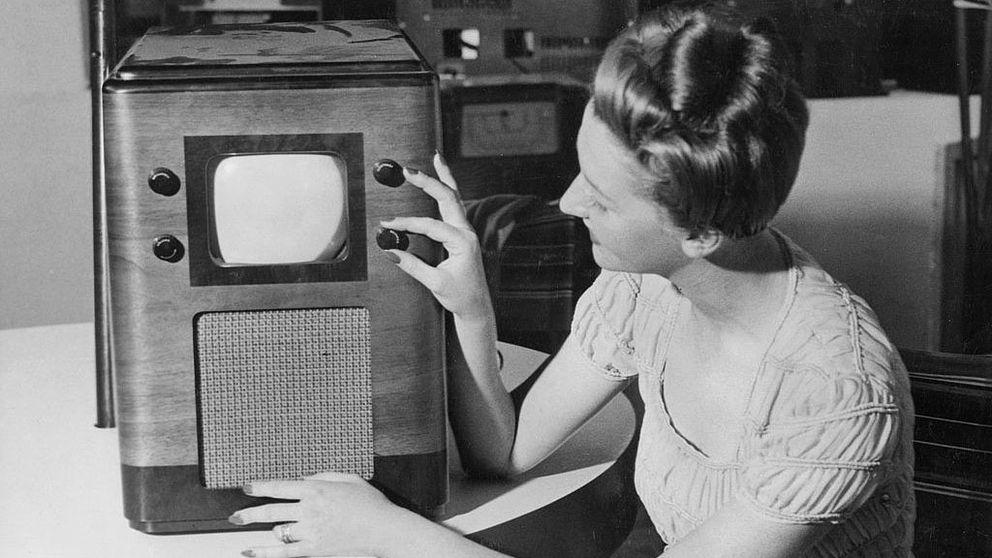 Svartvit bild av en kvinna som vrider på kanalratt på gammaldags tv.