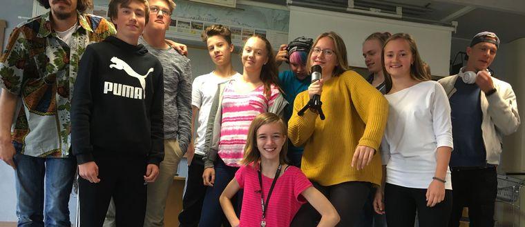 Ungdomarna som deltar i Popkollo poserar med en mikrofon.