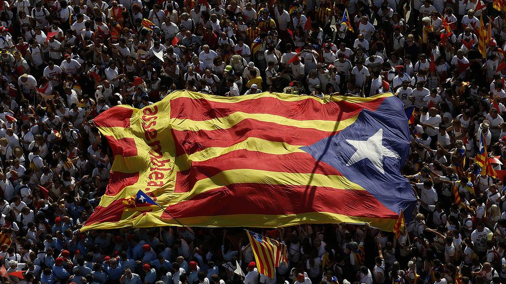 Ett hav av människor på ett torg. En stor katalansk flagga bärs av folket över deras huvuden.